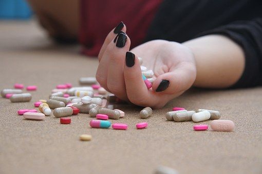 girl lying on her back, no face shown, hand full of pills that are also scattered all around her